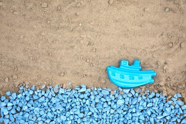 Colocar guijarros azules con barco en la arena Foto gratis