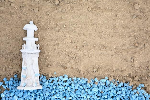 Colocar guijarros azules con faro en la arena Foto gratis