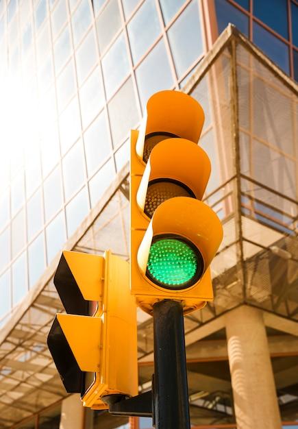 Color verde en el semáforo frente a edificio moderno. Foto gratis