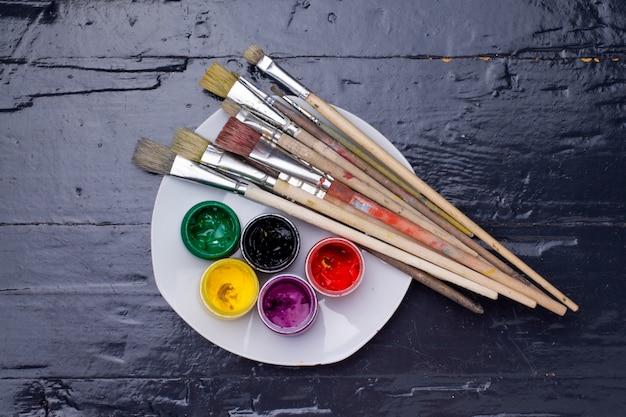 Colores en los frascos, pinceles y una paleta. Foto Premium
