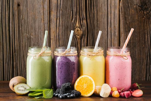 Colorida composición de frutas y batidos sobre fondo de madera. Foto gratis