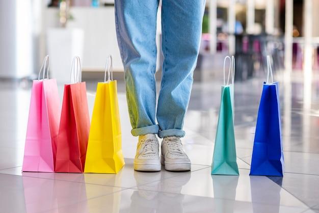 Coloridas bolsas de compras cerca de las piernas Foto gratis