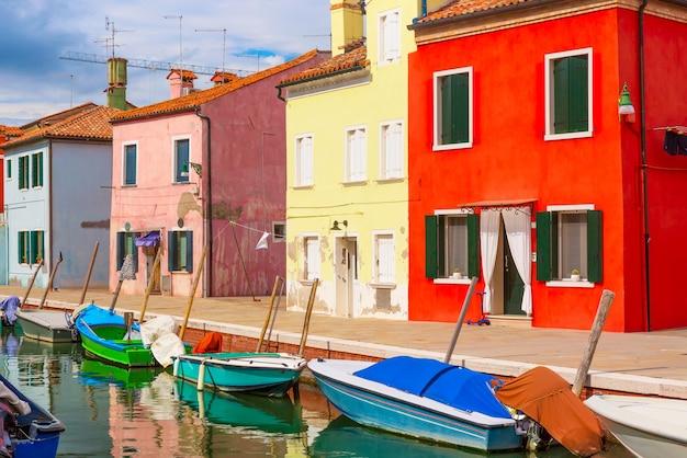 Coloridas casas y barcos en la isla de burano con cielo azul nublado cerca de venecia, italia Foto Premium