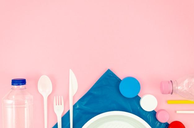 Coloridas cucharas y plato sobre fondo rosa Foto gratis