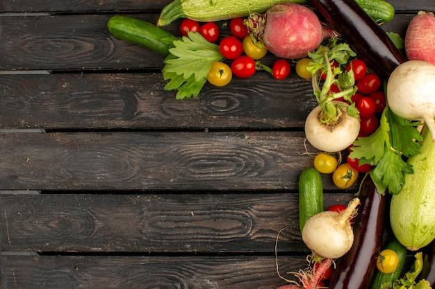 Coloridas verduras frescas en un piso de madera marrón Foto gratis