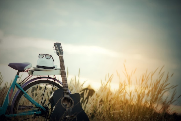 Colorido de bicicleta con guitarra en prado Foto gratis