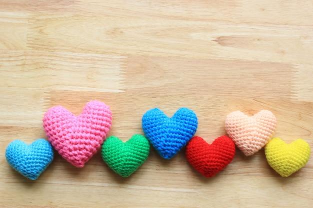 Colorido de corazón de ganchillo hecho a mano en la mesa de madera para el día de san valentín con copyspace Foto Premium