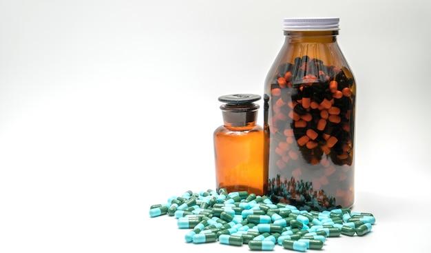 Colorido de píldoras de cápsulas de medicina antibiótica y dos botellas de ámbar, resistencia a los medicamentos, espacio de copia Foto Premium