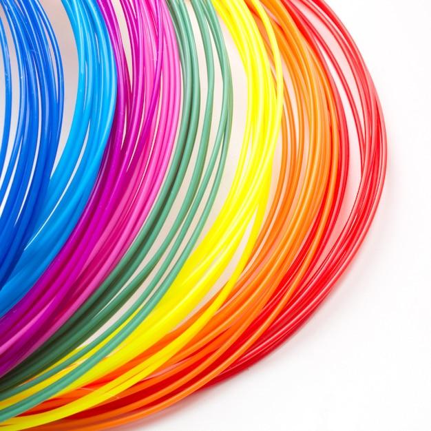 Coloridos filamentos de plástico arcoíris para pluma 3d en blanco Foto Premium