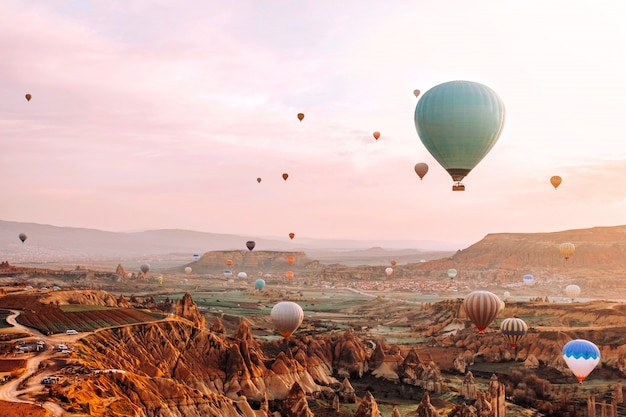 Coloridos globos aerostáticos volando sobre el valle al amanecer en capadocia Foto Premium