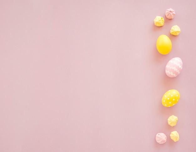 Coloridos huevos de pascua con dulces en mesa Foto gratis