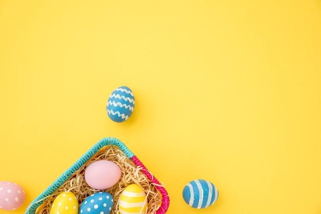 Coloridos huevos de pascua en una pequeña cesta en mesa amarilla Foto gratis