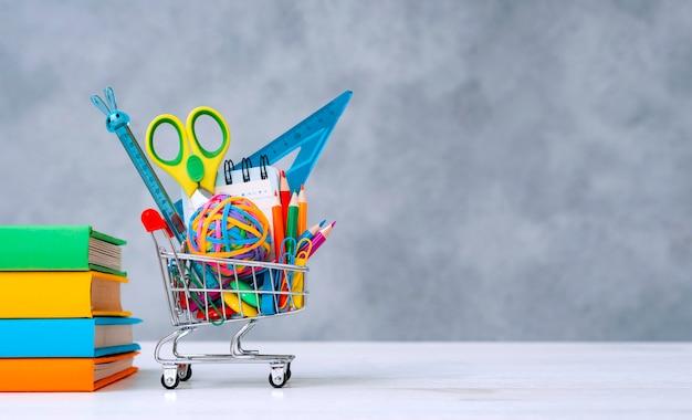Coloridos útiles escolares en la cesta de la compra sobre un fondo gris con una copia del espacio de texto. una pila de libros con portadas de colores. el concepto de regresar a la escuela para el nuevo año académico. Foto gratis