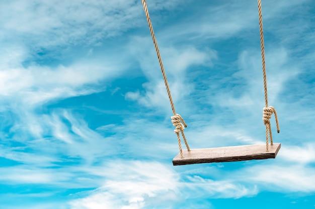 Columpio de madera con cielo azul pastel y nube. Foto Premium