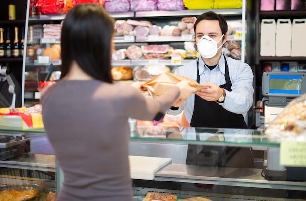 Comerciante que atiende a un cliente mientras usa una máscara Foto Premium