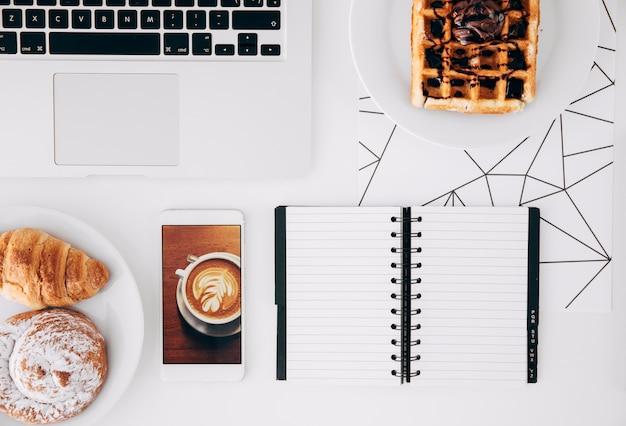 Comida al horno gofres de chocolate; teléfono móvil con pantalla de café; bloc de notas portátil y espiral en escritorio blanco Foto gratis
