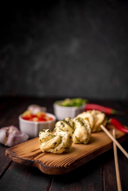 Comida asiática tradicional en tablero de madera con ajo y palillos Foto gratis