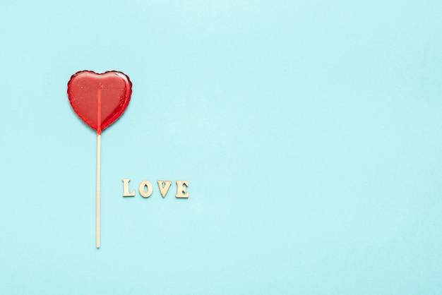 Comida y bebida, concepto de vacaciones. piruleta en forma de corazón para el amor día de san valentín con fondo azul. copia espacio Foto Premium