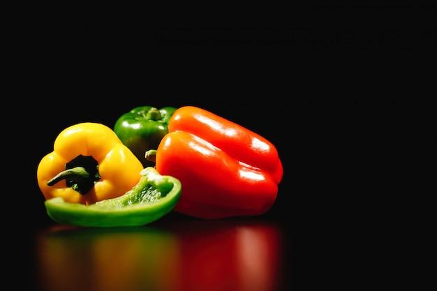 Comida fresca, sabrosa y saludable. pimientos rojos, amarillos y verdes aislados sobre fondo negro Foto gratis