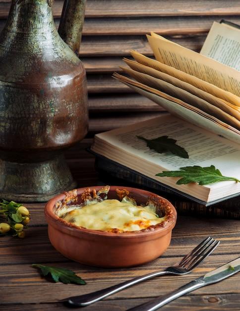 Comida guisada dentro de un recipiente de cerámica cubierto con queso derretido en la parte superior Foto gratis