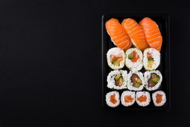Comida japonesa: sushi maki y nigiri en vista superior negra, espacio de copia Foto Premium
