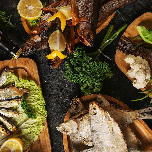 Comida mediterránea, pescado de arenque ahumado servido con cebolla verde, limón, tomates cherry, especias, pan y salsa tahini en la oscuridad. vista superior con un primer plano Foto gratis