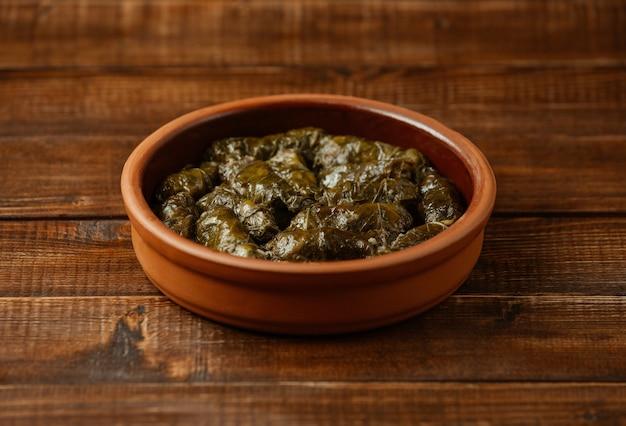 Comida nacional yarpaq dolmasi, hojas de uva con carne adentro, cocinadas dentro de un tazón de cerámica Foto gratis
