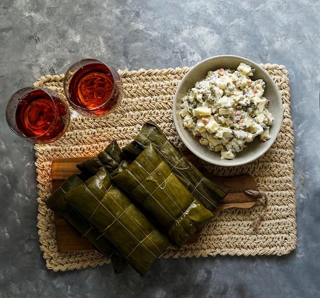 Comida navideña venezolana, hallacas, masa de maíz rellena de estofado de cerdo y pollo y ensalada de pollo Foto Premium