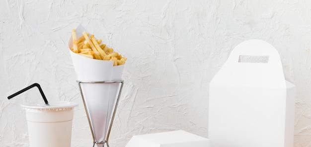 Comida rápida; taza de eliminación y paquete de alimentos se burlan contra la pared Foto gratis