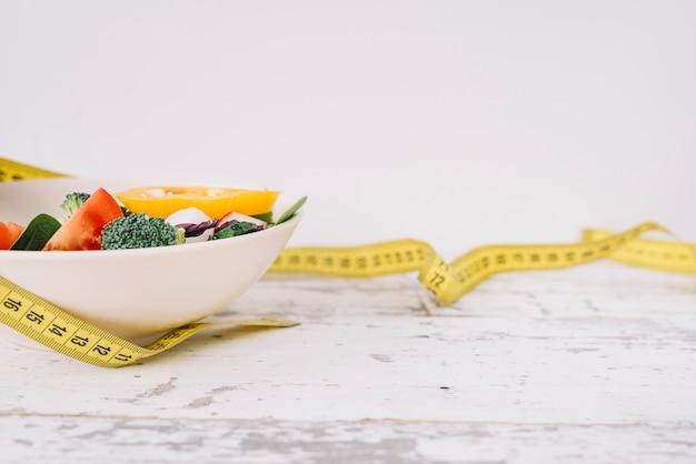 Comida saludable y cinta de medir Foto Premium