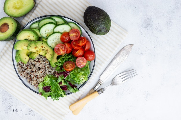 Comida sana. tazón de budha con quinua, aguacate, pepino, ensalada, tomate, aceite de oliva. Foto Premium