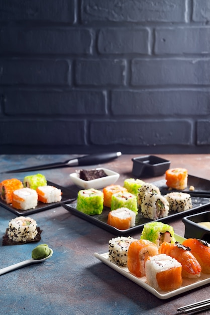 Comida tradicional japonesa sushi, rollos, palillos, salsa de soja sobre piedra de color Foto Premium