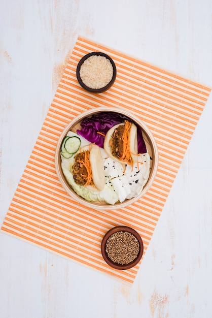 Comida tradicional de taiwán gua bao emparedado al vapor en vaporera con cuencos de arroz y semillas de cilantro sobre el mantel Foto gratis