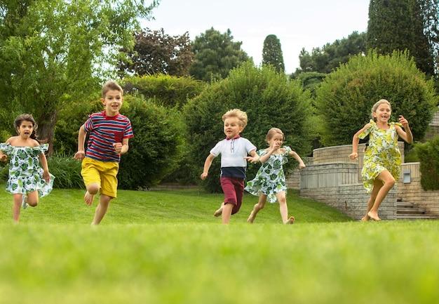 Comienzos divertidos. concepto de moda infantil. grupo de niños y niñas adolescentes corriendo en el parque. ropa colorida para niños, estilo de vida, conceptos de colores de moda. Foto gratis