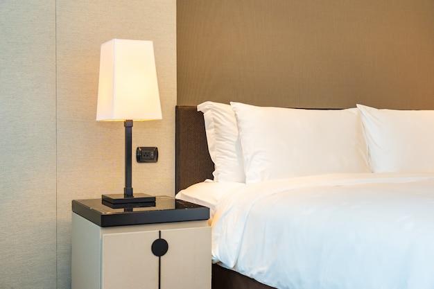 Cómoda almohada blanca y manta en la cama con lámpara de luz Foto gratis