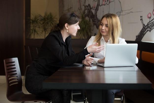 Compañeras de trabajo hablando en una cafetería Foto gratis