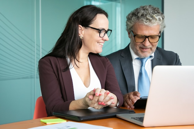 Compañeros alegres o socios de negocios reunidos y discutiendo el proyecto, sentados en el portátil abierto, usando la tableta, hablando y sonriendo. Foto gratis