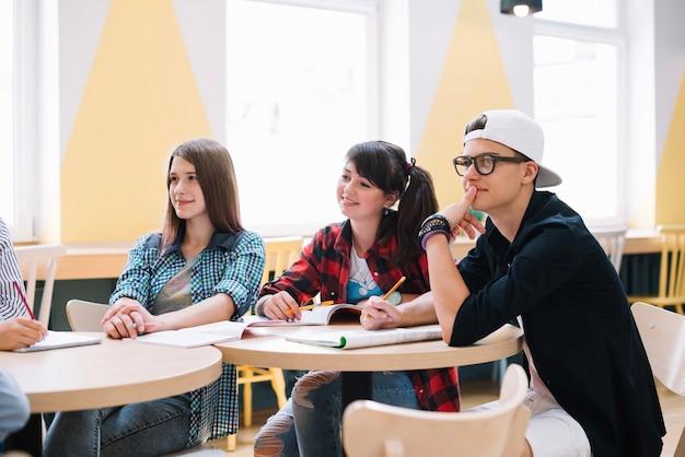Compañeros de clase que se sientan y que aprenden en el escritorio Foto gratis