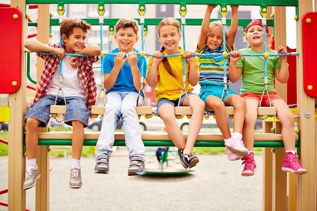Compañeros de clase sonrientes sentados en fila en el parque infantil Foto gratis