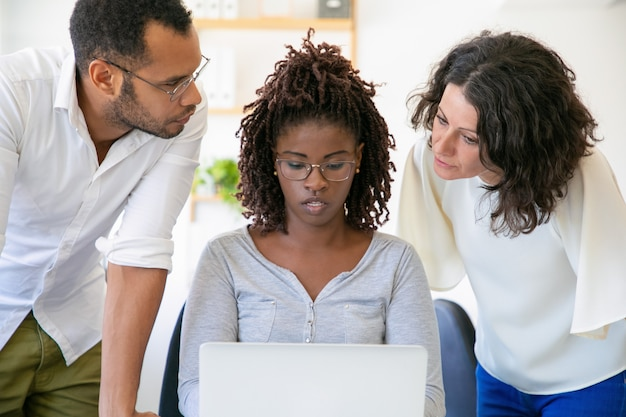 Compañeros confiados que hablan mientras trabajan con la computadora portátil Foto gratis
