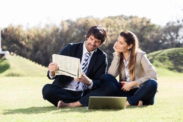 Compañeros de trabajo felices leyendo noticias al aire libre Foto Gratis