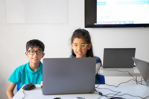 Compañeros felices en vasos sentados a la mesa juntos y usando la computadora portátil en el aula Foto gratis