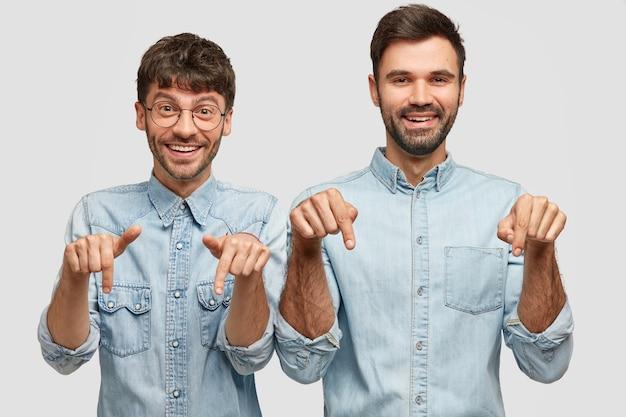 Compañeros de hombre alegre con expresiones positivas, señalar hacia abajo, involucrados en publicidad, vestidos con ropa casual Foto gratis