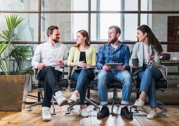 Compañeros jovenes de la compañía que se sientan en fila y que se hablan Foto gratis