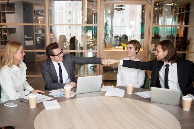 Compañeros o compañeros masculinos amigables, puños, golpes en la reunión del equipo Foto gratis