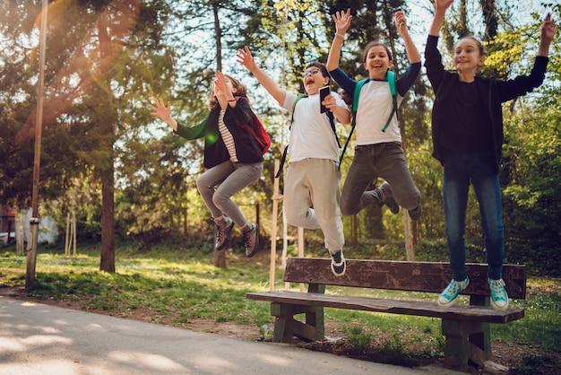 Compañeros saltando del banco en el patio de la escuela Foto Premium