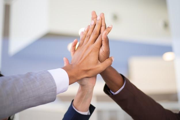 Compañeros de trabajo celebrando el éxito y uniendo manos Foto gratis