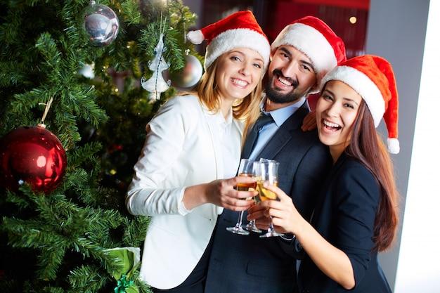 Compañeros de trabajo felices con champán celebrando la navidad Foto gratis
