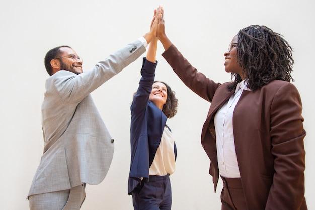 Compañeros de trabajo felices disfrutando del éxito del equipo Foto gratis