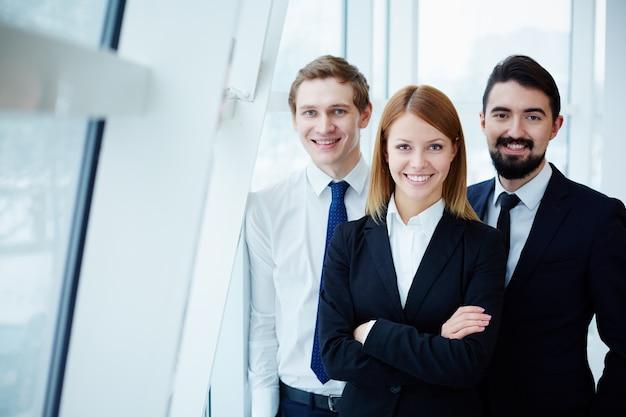 Compañeros de trabajo felices junto a la ventana Foto gratis